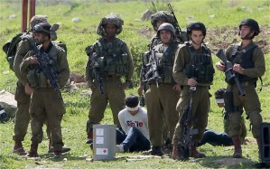 Israeli soldiers hold a Palestinian youth. Photo: AFP